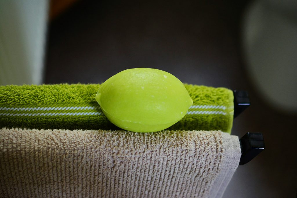 green lime-shaped soap on two towels. One is green, the other is brown.